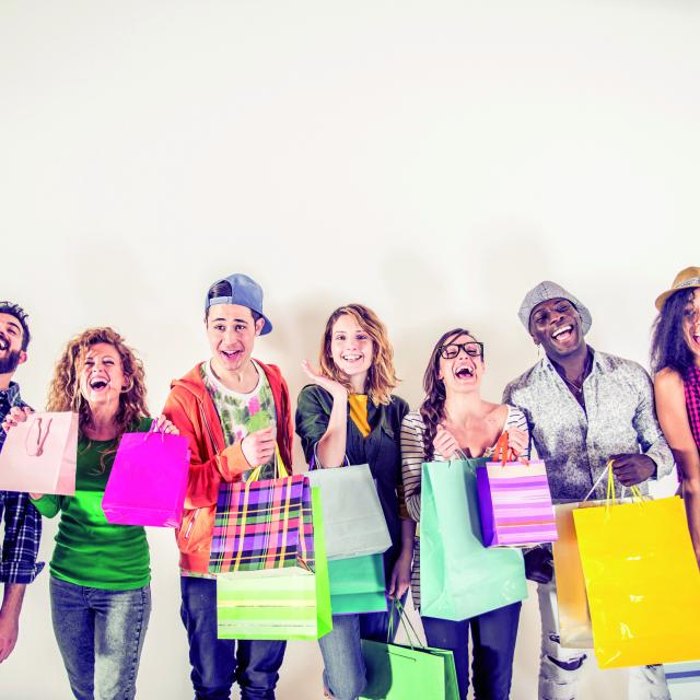 Multi-ethnic group of people holding colored shopping bags and laughing - Portrait of funny friends posing on white background