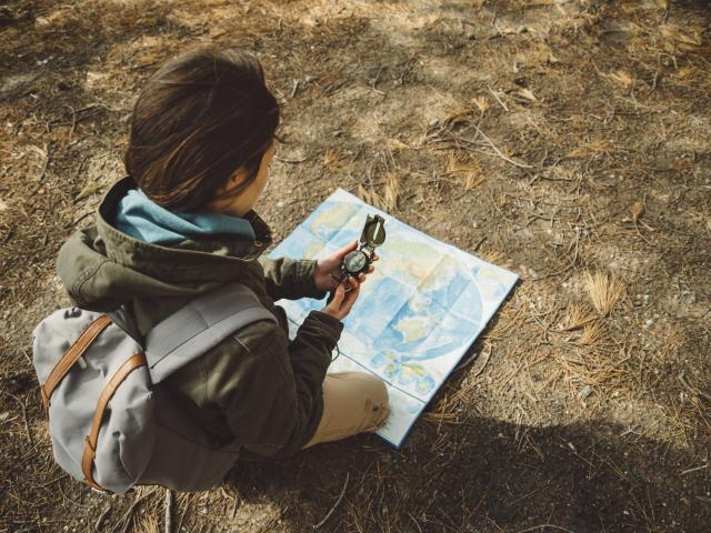 Traveler young woman with backpack searching direction with a compass on background of map in the forest. Focus on compass