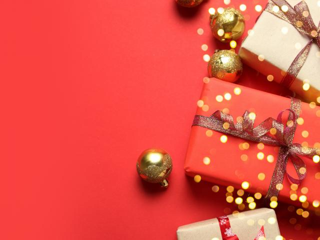 Christmas background with Gifts boxes, red ribbons, golden decorations on red background. Christmas, winter, new year concept. Flat lay, top view, copy space