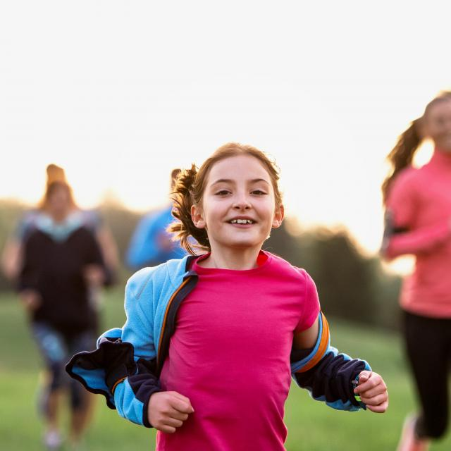 A portrait of small girl with large group of people running in nature.