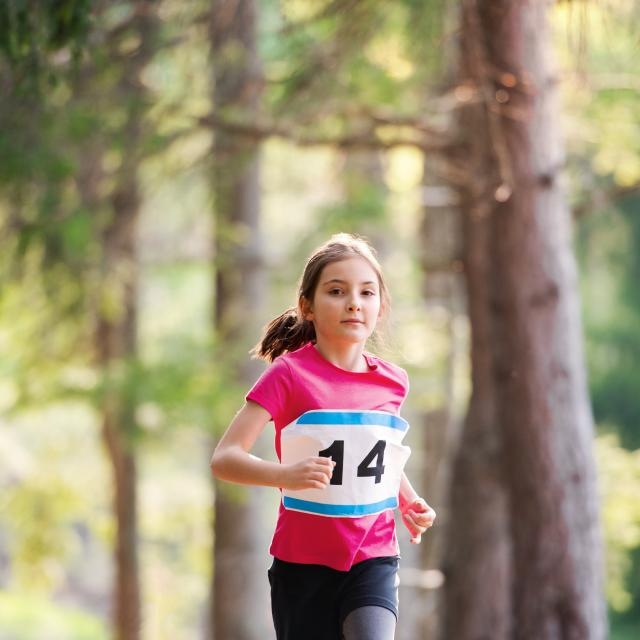 A front view of small child running a race competition in nature. Copy space.