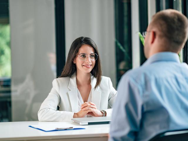 Smiling young corporate personnel manager talking to a male job applicant.