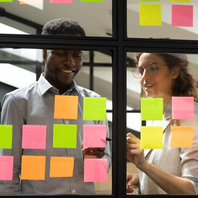 Multiracial colleagues developing business ideas use post-it notes view through glass, mates read written tasks shown on stickers attached on wall, effective way do work don't forget anything concept