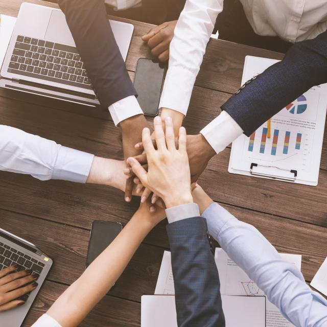Corporate unity. Multiethnic business team stacking hands together on meeting, top view