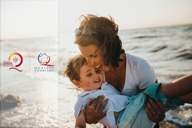 Femme tenant son enfant sur la plage