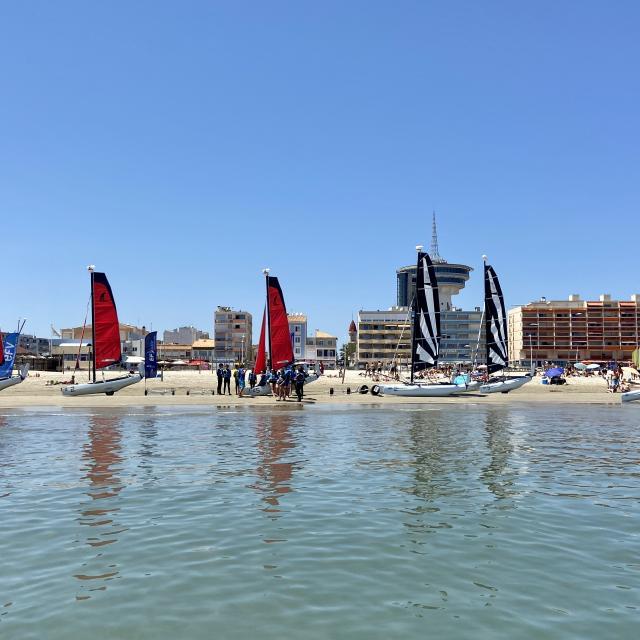 Bateaux à voile sur la plage avec les immeubles et le Phare de la Méditerranée en fond