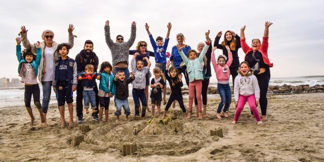 Parents et enfants devant un château de sable