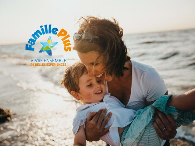 Mère tenant son enfant dans les bras avec le logo Famille Plus