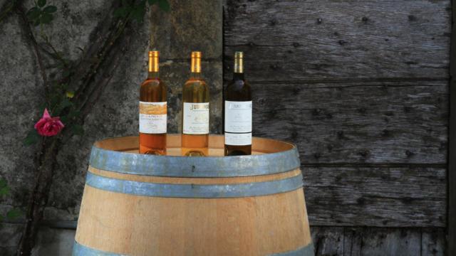 Trois bouteilles de vin blanc de Clos Guirouilh présentées sur un fût
