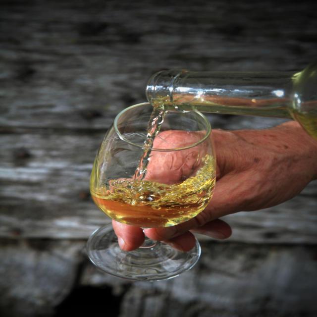 Deux mains servent du vin du Clos Guirouilh à Lasseube