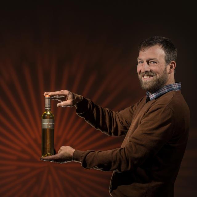 Producteur du Domaine Coustarret à Lasseube avec bouteille de vin