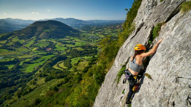Une sportive escalade la falaise d'Arguibelle à Lanne en Baretous