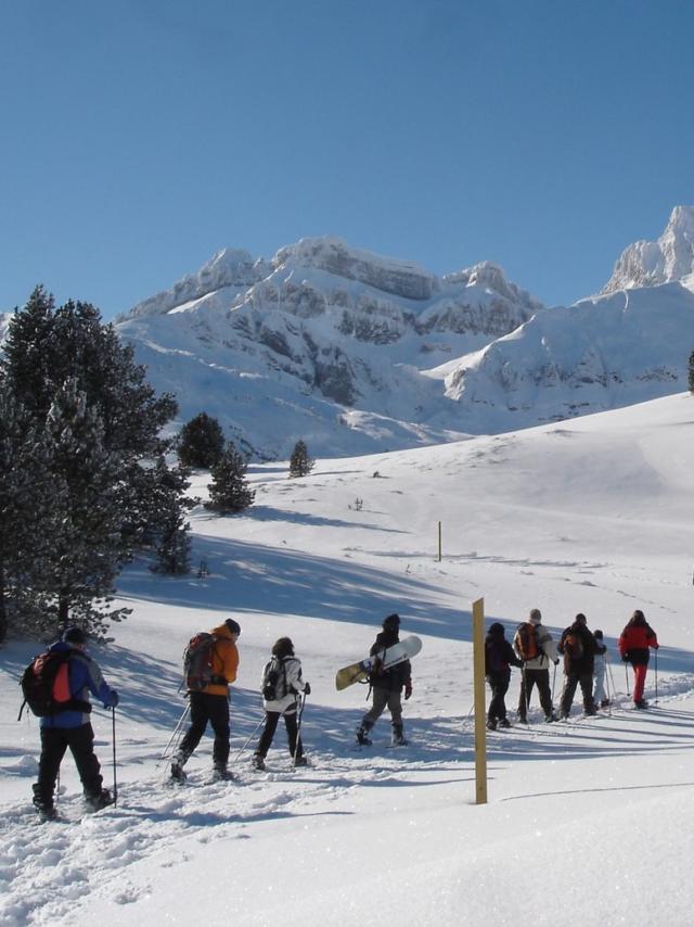 Groupe des personnes fait de la randonnée en raquettes à l'espace Nordique Du Somport