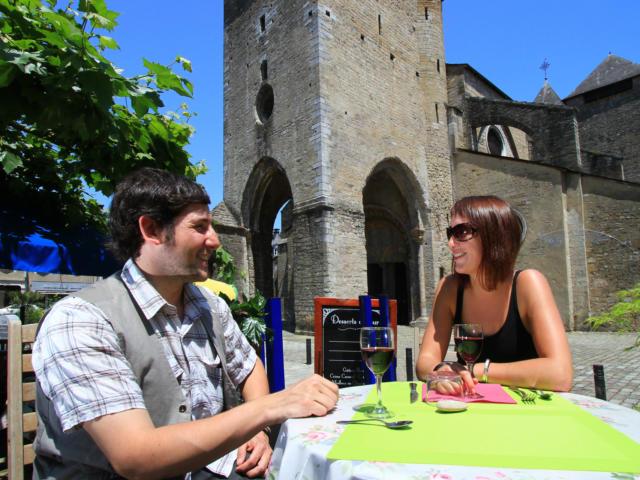 Couple atablé à la terrasse d'un restaurant sur la place de la Cathédrale d'Oloron Sainte-Marie
