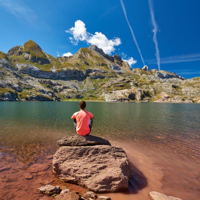 Randonneur assis sur une pierre au bord du lac d'Estaens