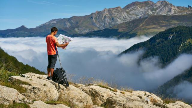Randonneur regarde une carte devant une mer de nuages