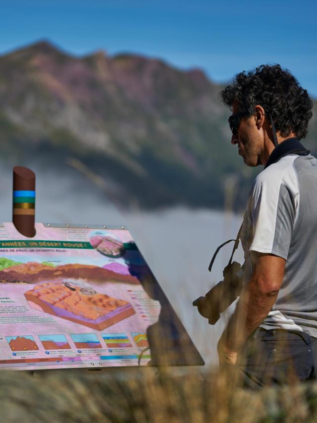 Géologie : randonneur observant un panneau d'information sur la route géologique de la vallée d'Aspe en Pyrénées Béarnaises