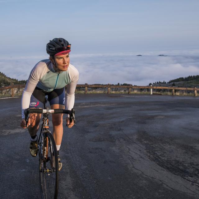 Cycliste en pleine ascension par un col de montagne sur le nuages