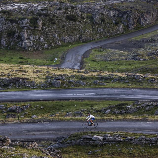 Une cycliste sur une route de montagne