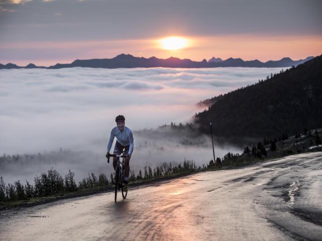 Une cycliste au sommet d'un col avec vue sur le coucher de soleil et les montagnes