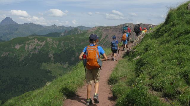 Sur le sentier du col de Saoubathou (vallée d'Aspe), on suit le guide géologue en marchant sur des roches rouges. Au fond, l'Ossau (Pyrénées béarnaises)