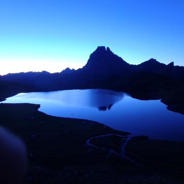 Lever de soleil pour les géorandonneurs sur la terrasse du refuge d'Ayous : en vedette, le pic du Midi d''Ossau et son reflet dans le lac l (Pyrénées béarnaises)
