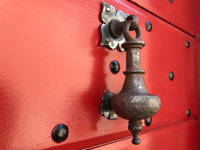 Aldabón antiguo sobre una puerta roja