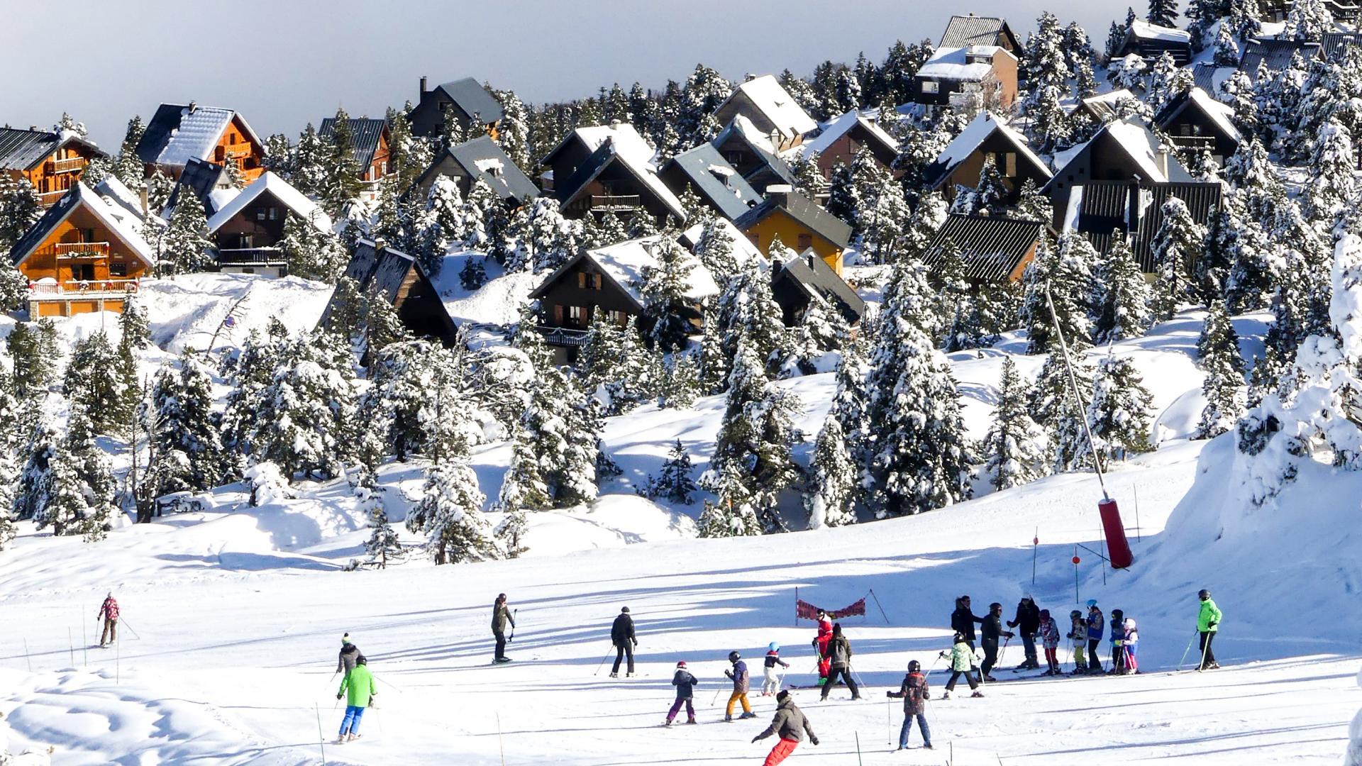 Pueblo de Chalets y grupo de esquiadores en La Pierre Saint Martin