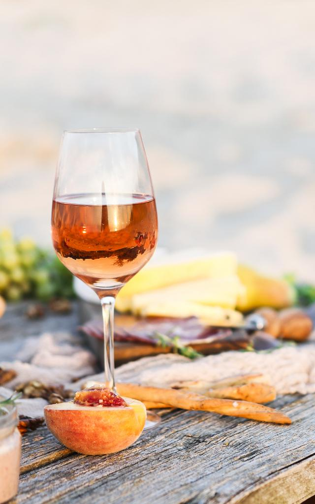 Glass of rose wine on rustic table. Food and drink background