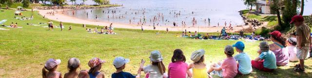 Enfants assis au bord du lac de la base de loisirs de Léry-Poses en Normandie