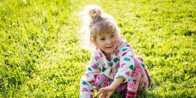 Petite fille jouant dans l'herbe < Soissons