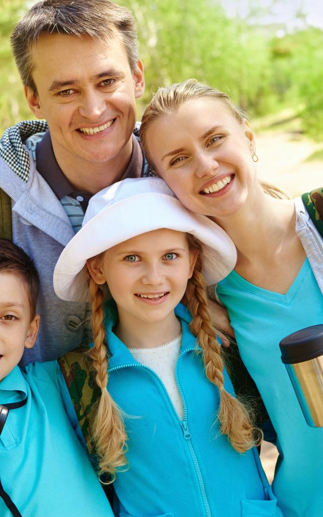 Portrait of family of travelers looking at camera in summer