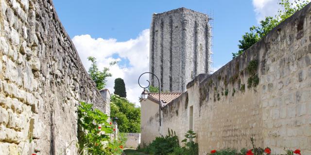 Tour Carrée de Loudun derrière une rue de coquelicots