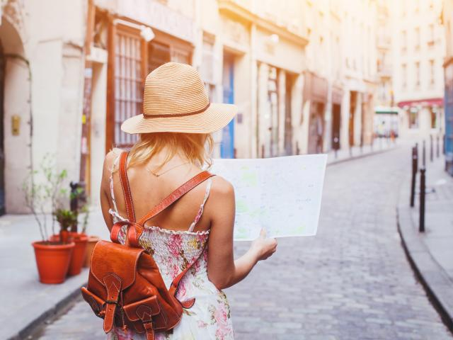 woman tourist looking at the map on the street of european city, travel to Europe
