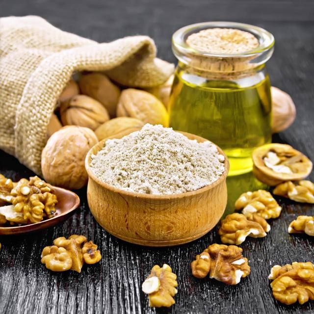 Walnut flour in bowl, nuts on a table, in spoon and in a jute bag, butter in glass jar on background of dark wooden board