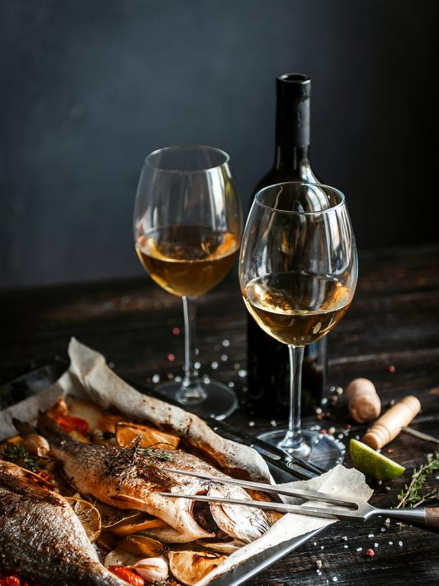 dinner concept for two. two glasses of white wine, baked fish.