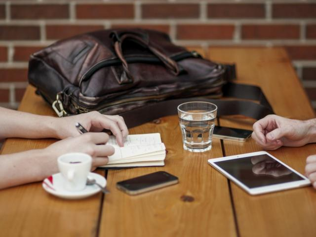 Friends Sitting In Cafe Writing In Notebook With Digital Tablet And Coffee Cup