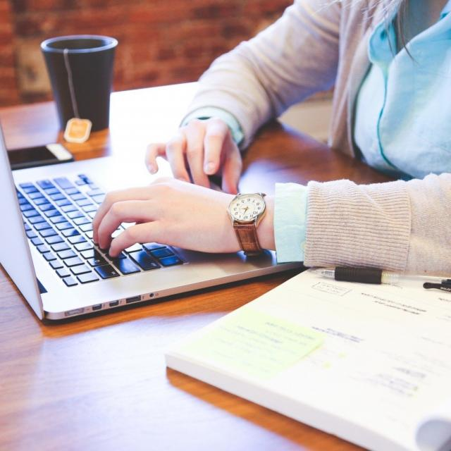 Woman Sitting At Table And Using Laptop With Tea Cup In Background