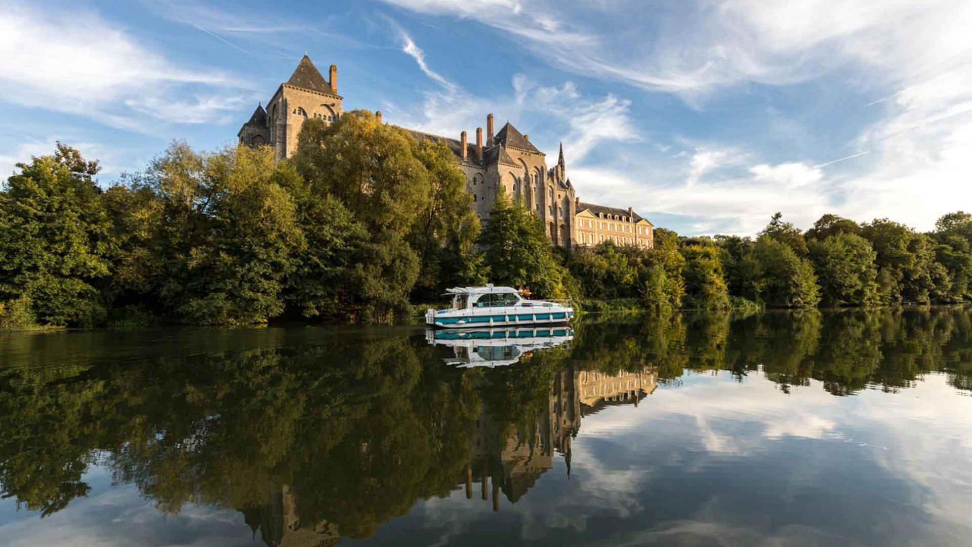 Bateau habitable d'Anjou Navigation passant devant l'Abbaye de Solesmes navigant sur la rivière Sarthe