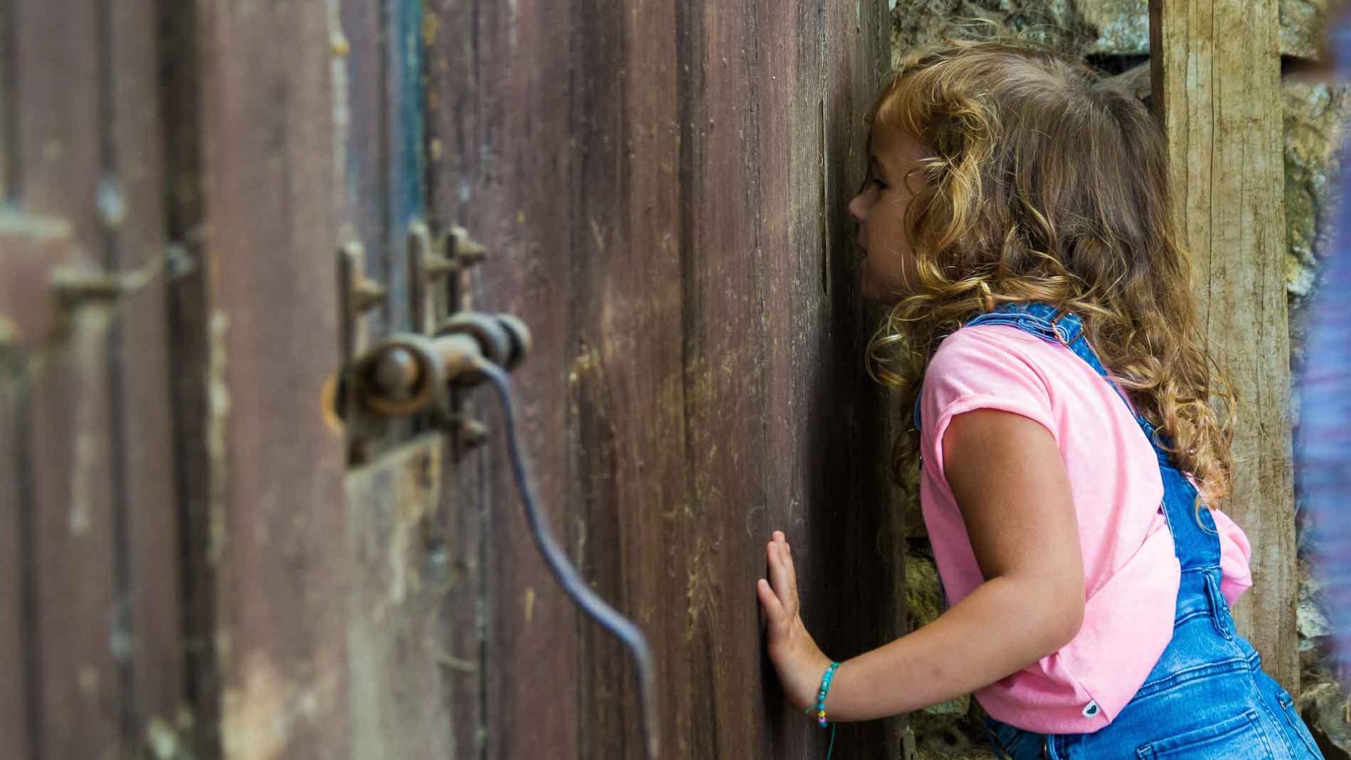Buller à la campagne - Petite fille regardant par une porte de grange