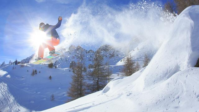 Snowboard en poudreuse en bord de piste. Au premier plan snoboarder qui vient de sauter une petite bosse naturelle en poudreuse en bord de piste. En arrière plan, sur la droite les crêtes de l'Eyssina et sur la gauche le