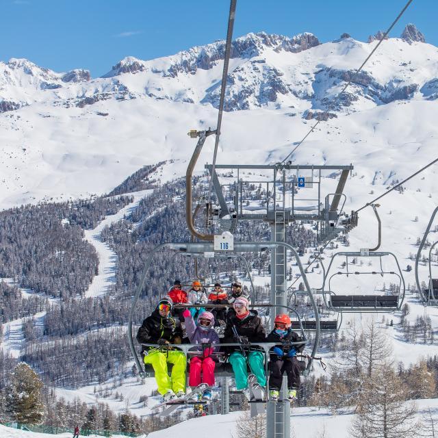 Famille sur un télésiège permettant d'accéder sur les hauteurs du domaine skiable