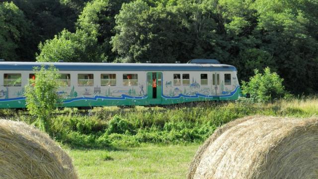 Train touristique avec en premier plan des bottes de paille à la campagne à Thoré-la-Rochette