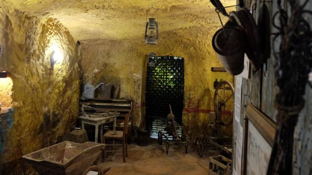 Exposition d'objets autour de la vigne et des obkets anciens dans une cave troglo à Trôo