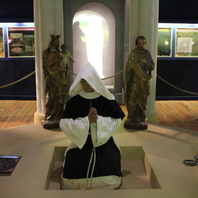 Représentation de la prière d'un prêtre au centre de découverte de Moyen-âge
